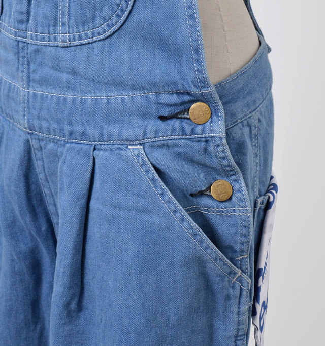 ウエストにはタックが施され、女性らしい柔らかな印象をプラス。両サイドにはポケットや、着脱しやすいようにボタンが付いています。