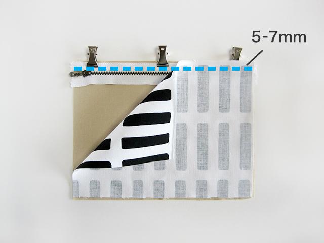 (2) (1)と表地を中表に重ねます。 金具が当たらないように気をつけながら、上から約5~7mmステッチを端から端までかけて、縫い合わせます。 ※3つを一度に縫うのが難しい場合は、裏地とファスナーを先に縫い付けてから表地を縫い合わせてもOKです。