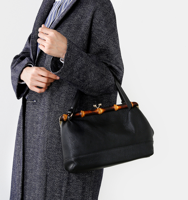 収納力たっぷり、 それでいて女性らしさも きちんと持ち合わせた 美しいバッグです。  がま口部分には味わいのある バンブーがあしらわれ、 レザーの素材感と 一緒になって深みのある 表情を見せてくれます。  ショルダーとハンドバッグの 2way仕様で使い勝手はもちろん◎