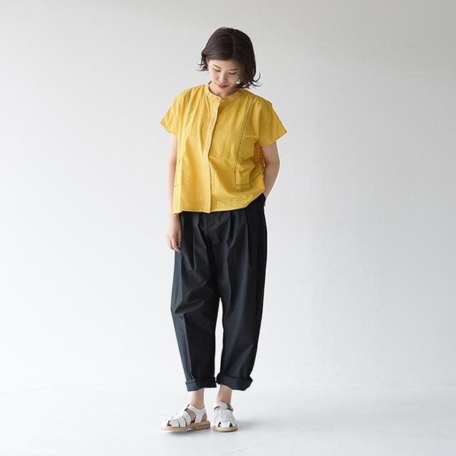 夏らしい明るい黄色のブラウスを着用していますが、シンプルに黒のパンツを合わせキレイめにまとめています。足元は重くなりすぎないように、白のグルカサンダルを履いて品よく仕上げています。